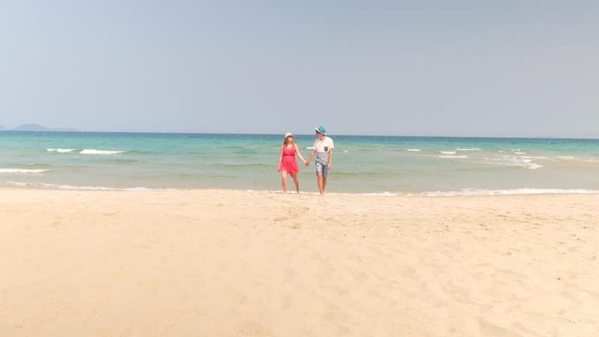 Lovely caucasian couple walking on sandy beach by the camera. Beautiful pregnant woman and man holding hands. | Shutterstock HD Video #16172044