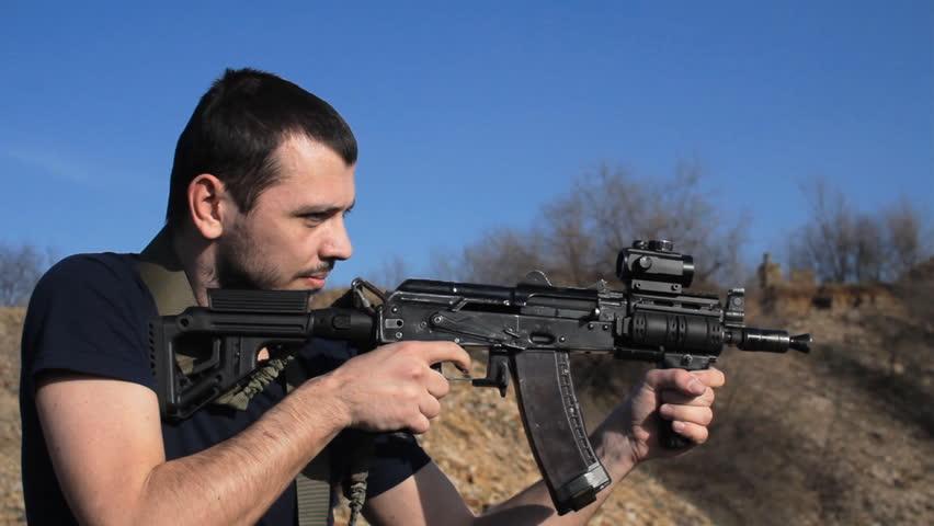 man firing customised russian machine gun, medium