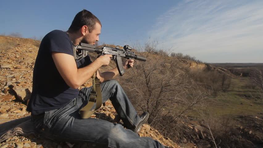 man firing customised russian machine gun, wide