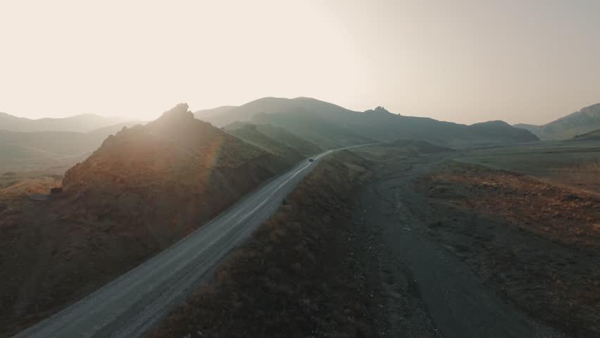 Drone flies over road between mountains on sun set follows a black car.