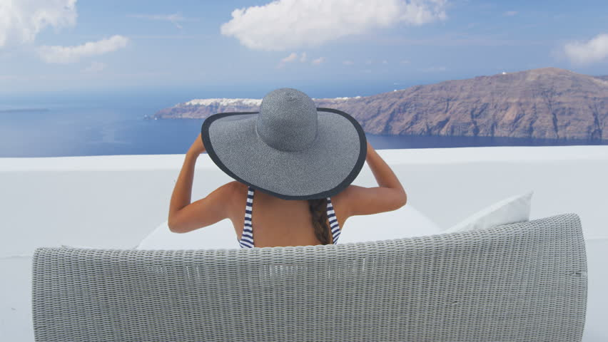 Vacation travel woman relaxing enjoying Santorini looking at famous view of Caldera. Young lady lying down on sun bed sofa lounge chair on holidays. Amazing view of sea. Europe tourist destination.