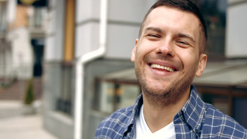 Portrait of happy cute caucasian man smiling in city Slow Motion  | Shutterstock HD Video #16199149