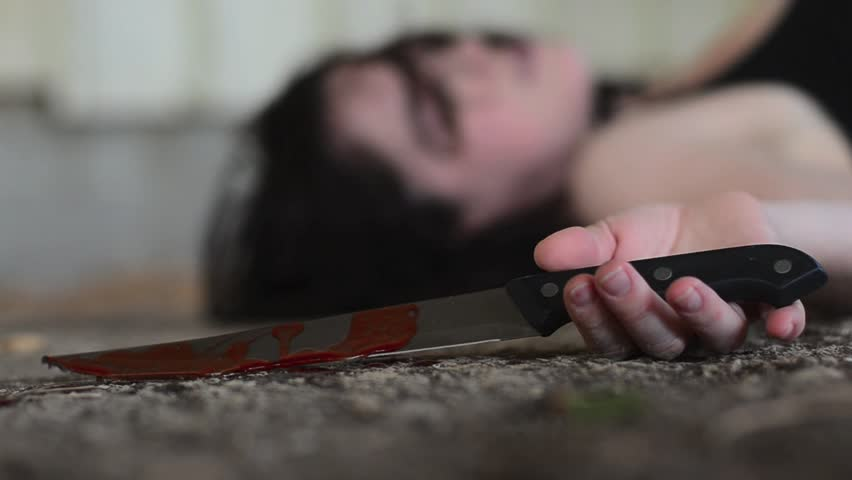 Conceptual footage of a dead woman holding a sharp knife covered with blood.