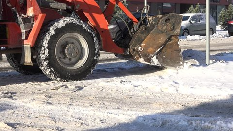 VILNIUS, LITHUANIA - JANUARY 11, 2016: Snow plow machine removing snow from city street after snowstorm blizzard in winter time on January 11, 2016 in Vilnius, Lithuania. Static shot. 4K
