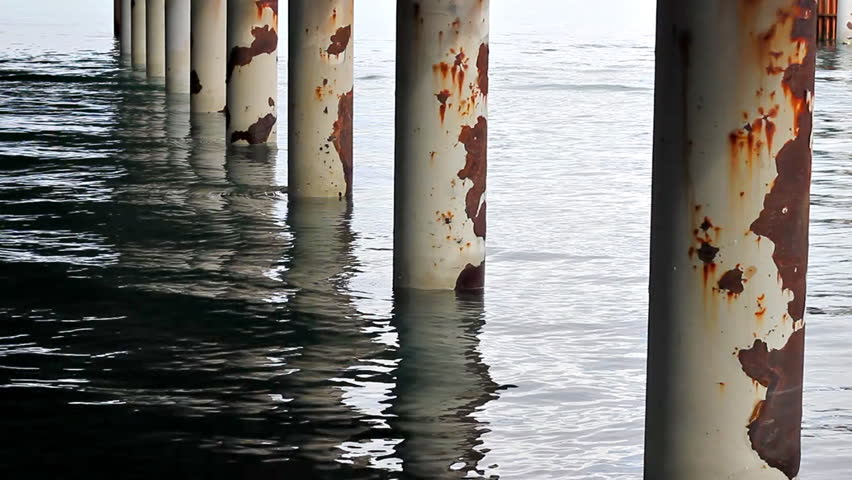 Water of the bay flowing around large rusty metal pier pillars.