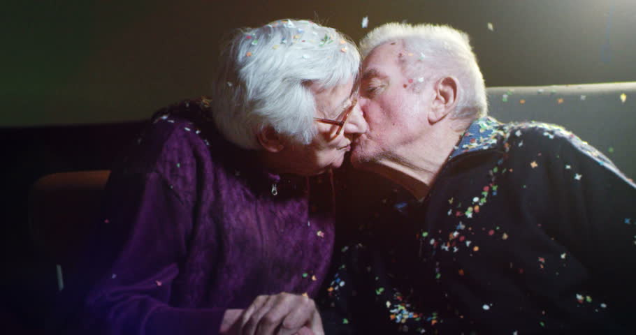 old tenderly couple at 90 birthday having fun with confetti and kissing in slow motion