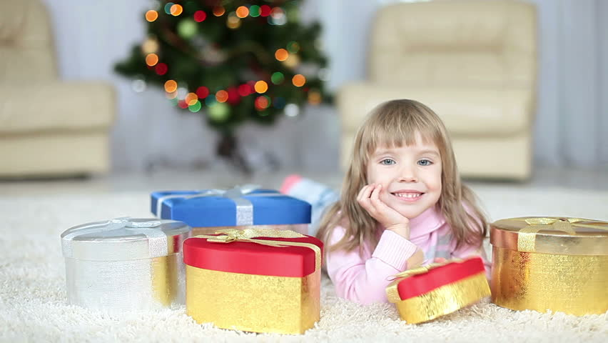 Child with a  gifts lying on the carpet. Looking at camera