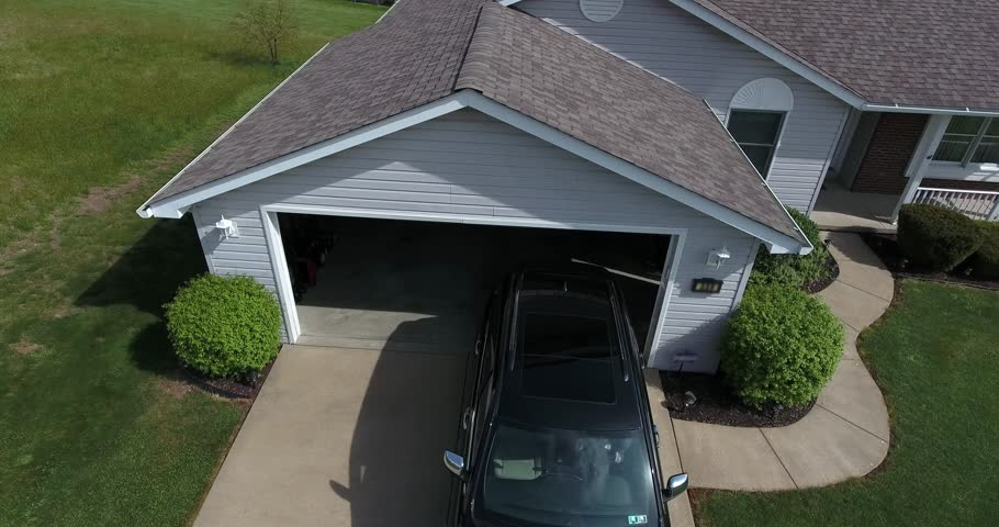 A high angle view of a vehicle pulling out of a garage.