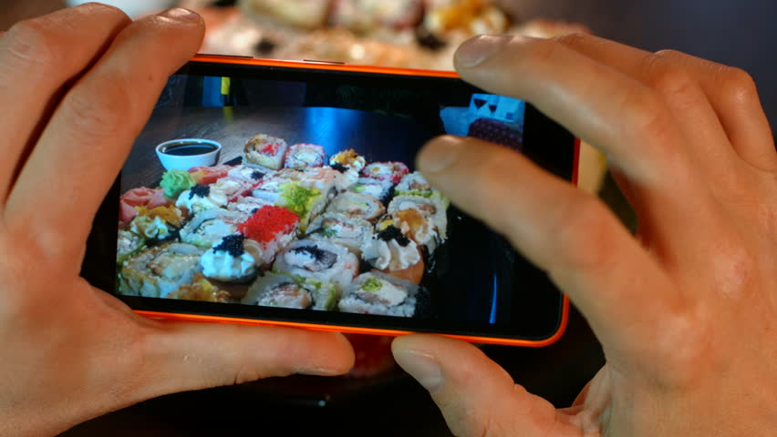The man on the smartphone photography food seafood cooking sushi Asian cuisine. 4K 30fps ProRes (HQ) #16293304