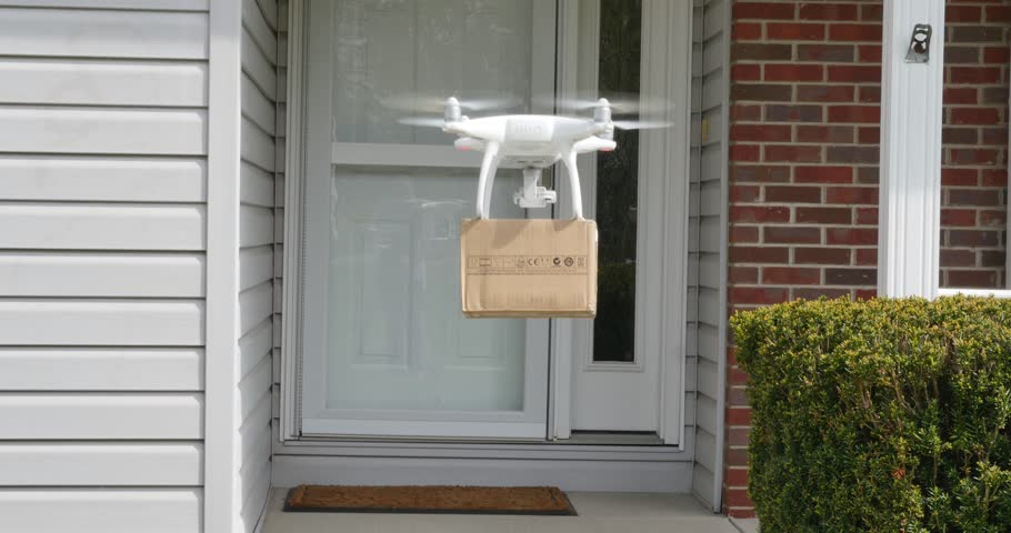 A small drone delivers a package to a residence.   | Shutterstock HD Video #16312966