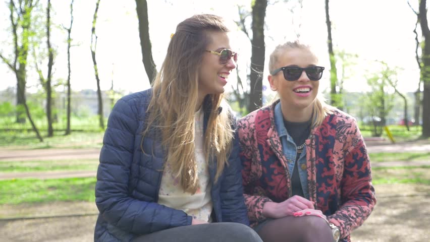 Two girl sitting on the bench in the park and having a conversation. | Shutterstock HD Video #16327027