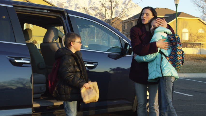 2 Kids get out of minivan and hug mother before running off to school