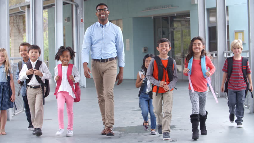 Male teacher walking in corridor with elementary school kids | Shutterstock HD Video #16355911