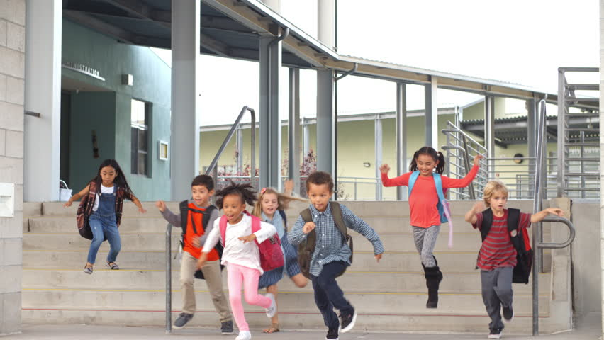 Young school kids jumping down steps as they leave school #16356886