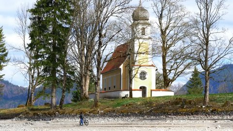 country church in spring, biker walks in front, Bavarian Alps Germany