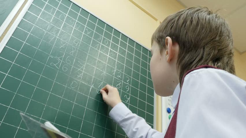 School boy solves math on the blackboard at primary school, 4k shot | Shutterstock HD Video #16393228