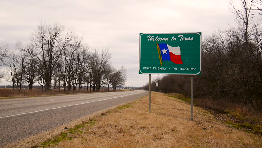 TEXAS, USA - 28 JAN 2014: View of Texas Welcome sign in the road with cars passing
