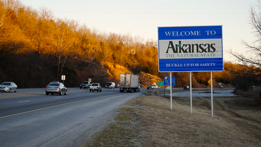 ARKANSAS, USA - 28 JAN 2014: View of Arkansas welcome road sign with vehicles passing by