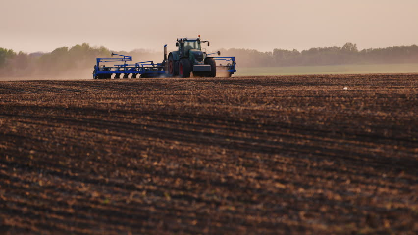 Tractor with drill goes through the field, carried out in spring seeding | Shutterstock HD Video #16413190