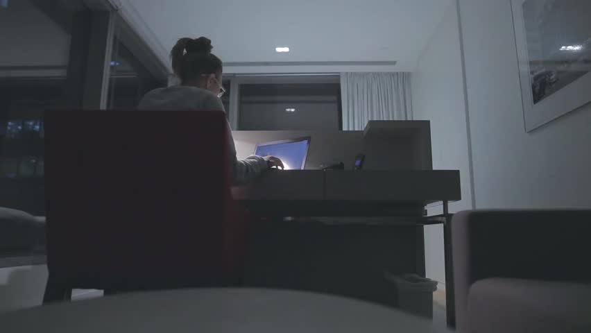 Young concentrated woman,  sitting in her room or office with french windows in the dark at the lamp.Studies late at night.Staying up late. Overworking.  Working late on laptop. #16414864