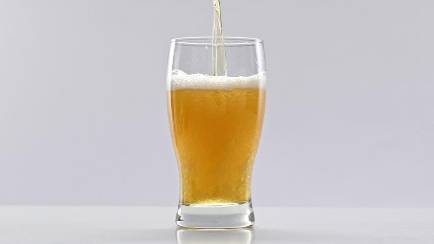 Beer is pouring into glass on white background. Slow motion