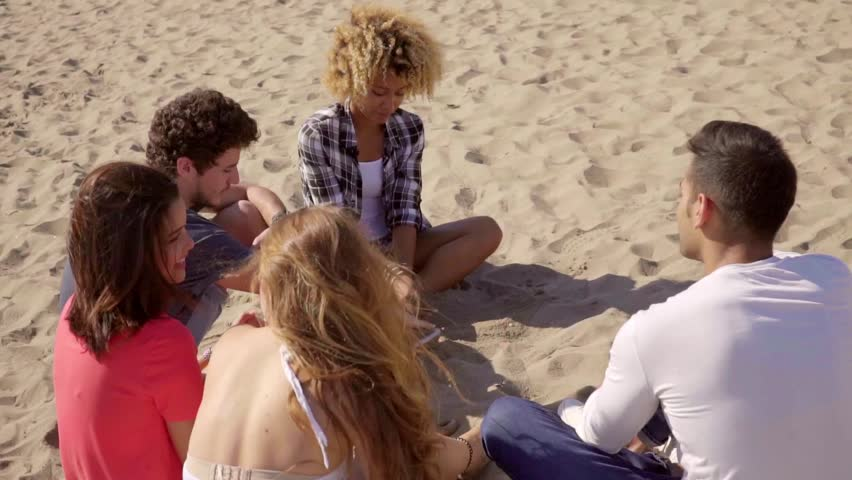 Group of friends sitting talking on the beach | Shutterstock HD Video #16449091