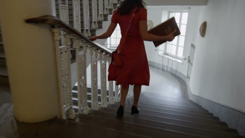 Girl  in a hurry  running down the staircase  at the university