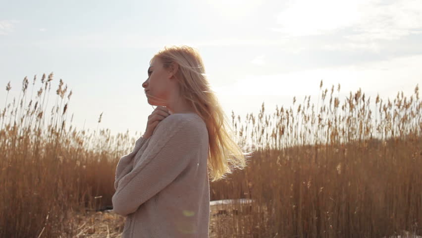 woman standing in the field of long grass in the lights of a sun   Shutterstock HD Video #16456624