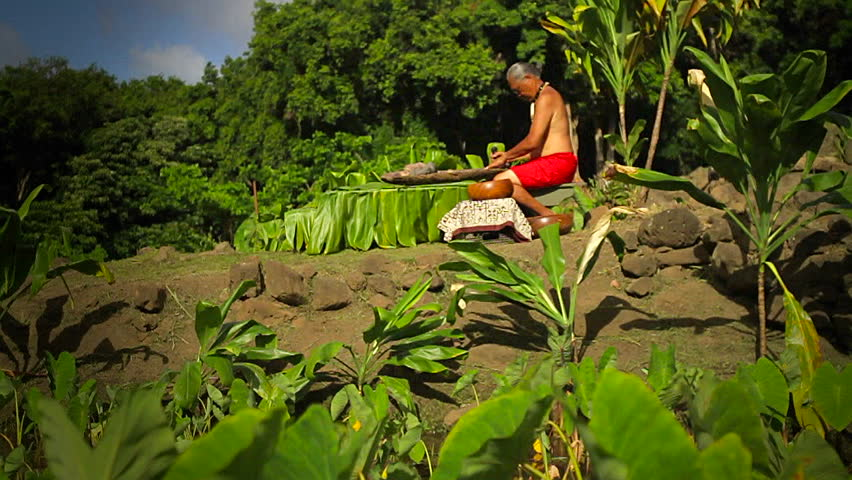 HAWAII - CIRCA 2010: A shaman sits on rocks and works.