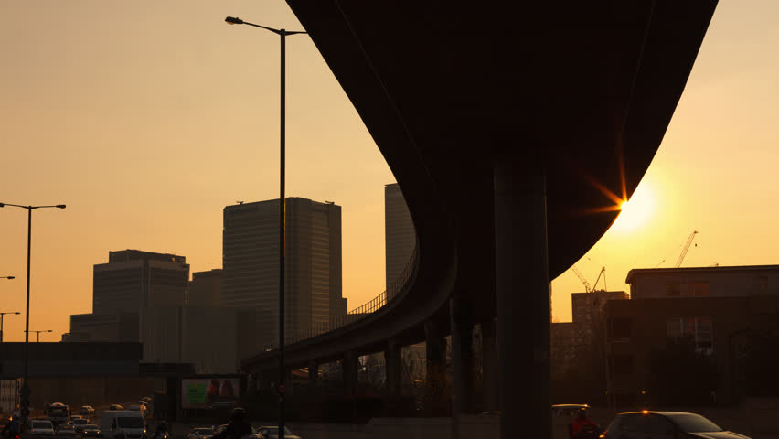 London, UK - 2016.03.17.: Canary Wharf Hyper-Lapse, Day to Night Time-Lapse on the Aspen Way. Motion time-lapse from the East India DLR station. Strong, misty and dusty orange sunset.