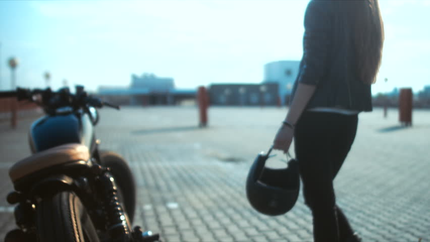 Young sexy Caucasian female biker walking towards her custom cafe racer motorcycle with helmet in hands. 60 FPS slow motion. Blackmagic URSA Mini