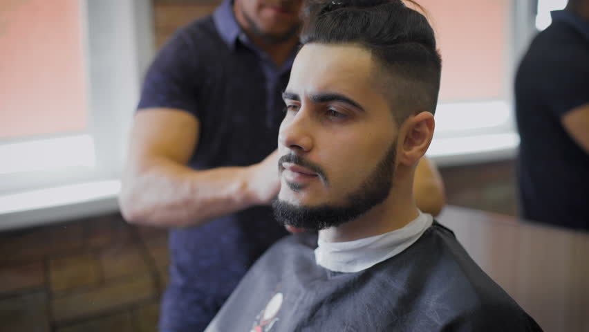 Young, brave hipster in your favorite barber shop. Master engaged in his beard, uses a trimmer to shape according to the latest trends. | Shutterstock HD Video #16521781