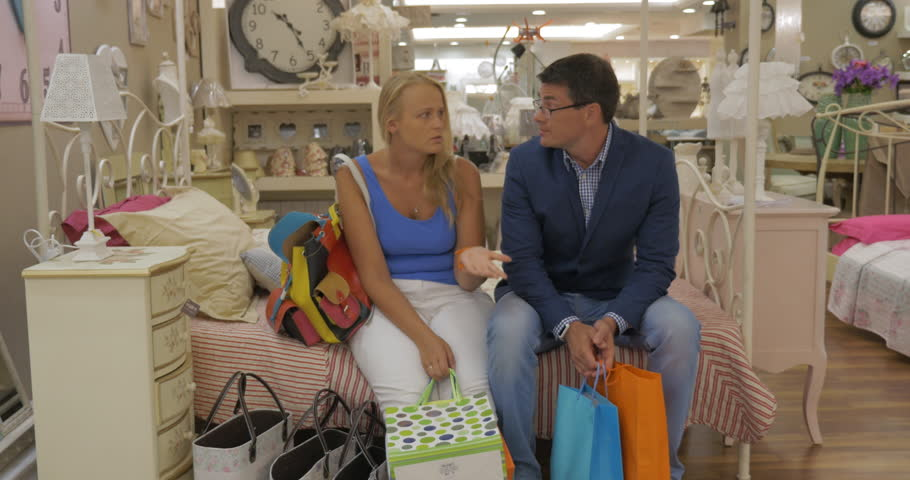 Family couple with bags sitting on the bed in the store and having a strict talk. Man expressing his annoyance towards womans shopping