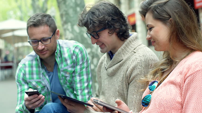 Friends using electronics and talking while sitting in the city, steadycam shot  | Shutterstock HD Video #16542427