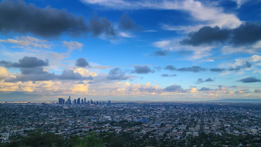 Storm clouds passing city of Los Angeles skyline changing from day to night. Zoom in. 4K UHD Timelapse.