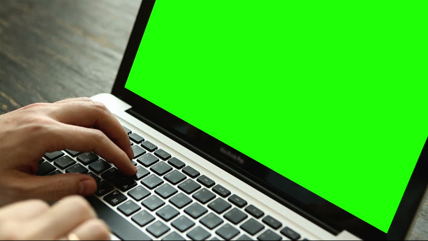 Hand of a man working at laptop computer typing on a keyboard on dark desktop. Close up view with green screen Royalty-Free Stock Footage #16546051