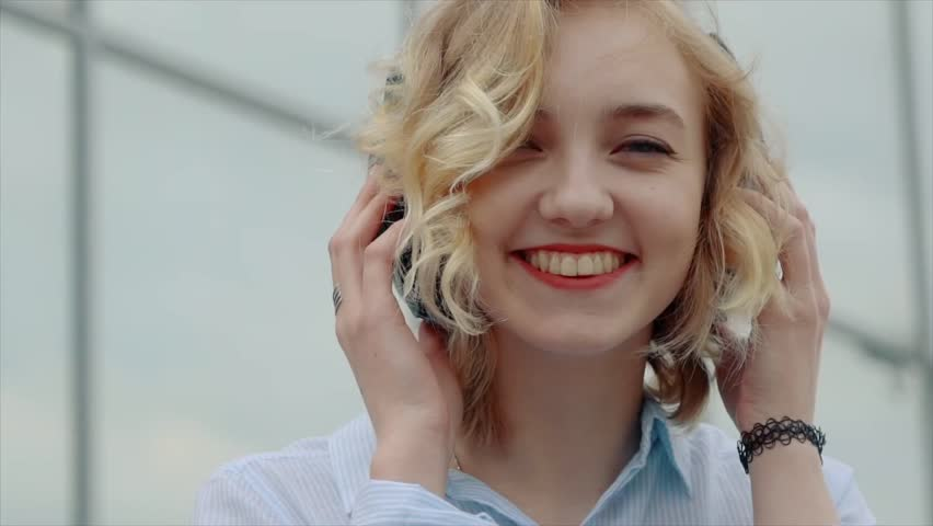 Smiling young blond woman standing outside with headphones | Shutterstock HD Video #16553119