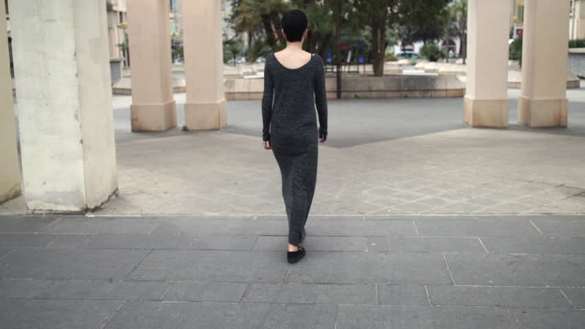 Female wearing in maxi dress and casual slip-on platform shoes. Holding mobile phone in her hand. Lady goes by column and palm trees | Shutterstock HD Video #16570981