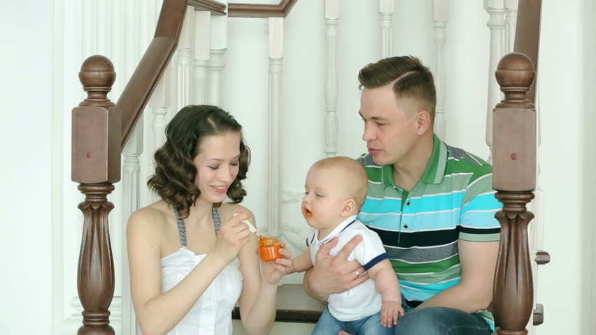 The mother feeds the child, and dad is holding him. Happy family. Mom dad and 6 month old baby. Family sitting on the stairs at home.   Shutterstock HD Video #16575628