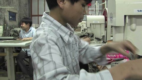 CHINA - CIRCA 2009: Asian youths sew in a factory in China circa 2009