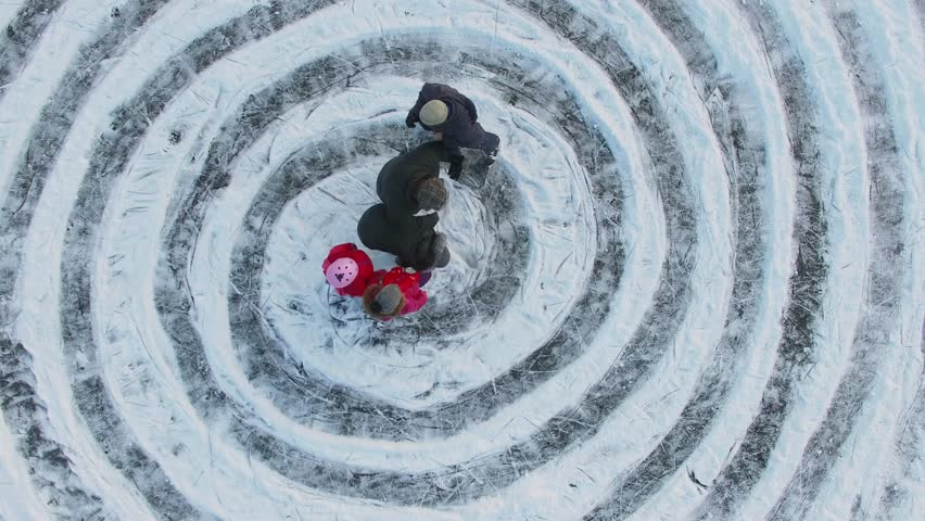 Children and parents start slide by ice spirals near name Ann at winter day. Aerial view