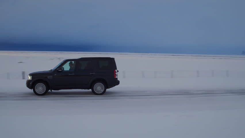 Iceland - March 2016: A black van drives down a snowy Iceland road, the sunset glistens in the distance | Shutterstock HD Video #16644628