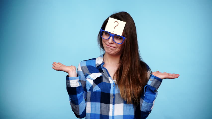Woman confused thinking seeks a solution, paper card with question mark on her head. Doubtful young female studio shot blue background. 4K ProRes HQ codec #16653349