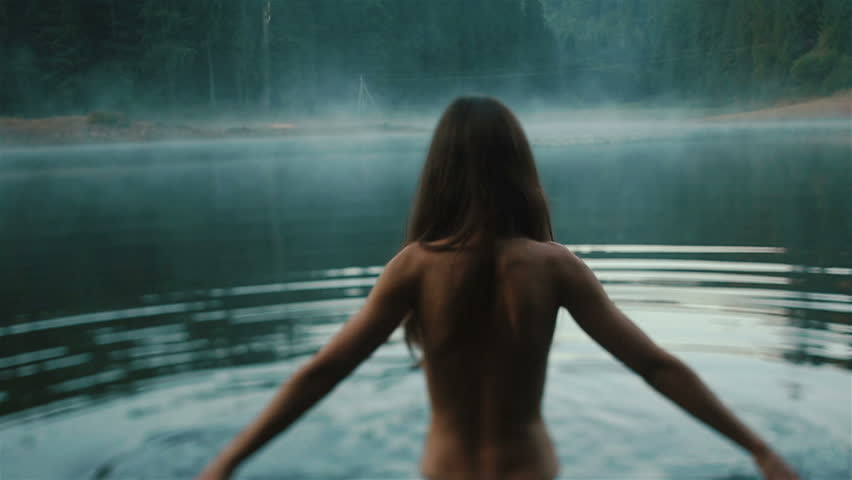 Beautiful naked fairy or mermaid with long dark hair in the mystical foggy mountain lake on back view. Fantasy magic world in mountains