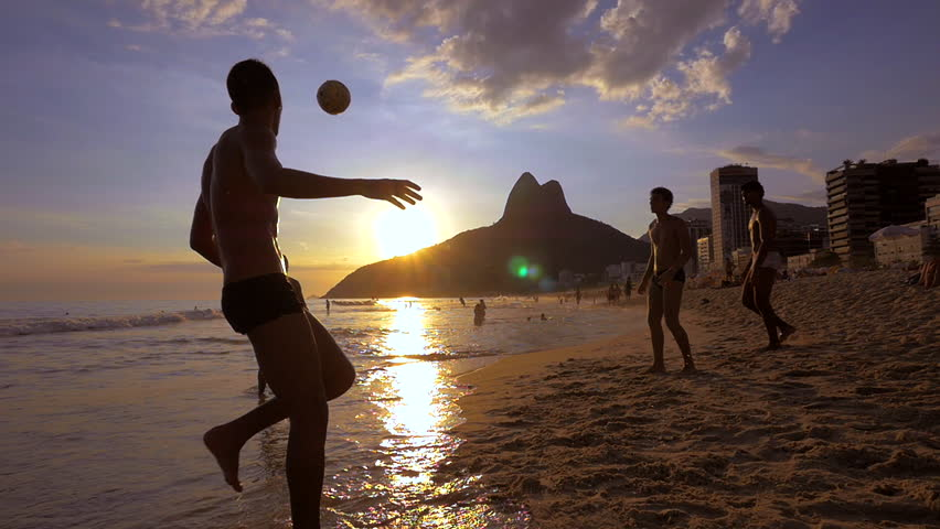 Rio de Janeiro, Brazil - Circa February, 2016: Slow motion shot of locals playing ball at sunset at famous Ipanema beach in Rio de Janeiro, Brazil.