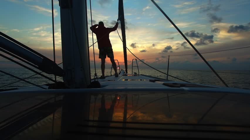 Young man standing with his back on the bow sailing yacht and looks forward in the course of the boat. Beautiful sunset sky in background. Look into the distance. Standing at deck of boat. #16703404