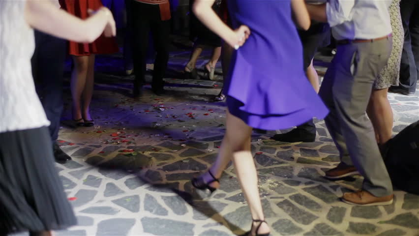 Legs of drunk people performing circle dancing all together at a night party