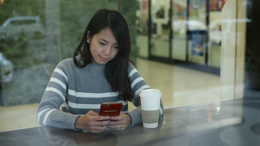 Young woman using smartphone in cafe | Shutterstock HD Video #16737763