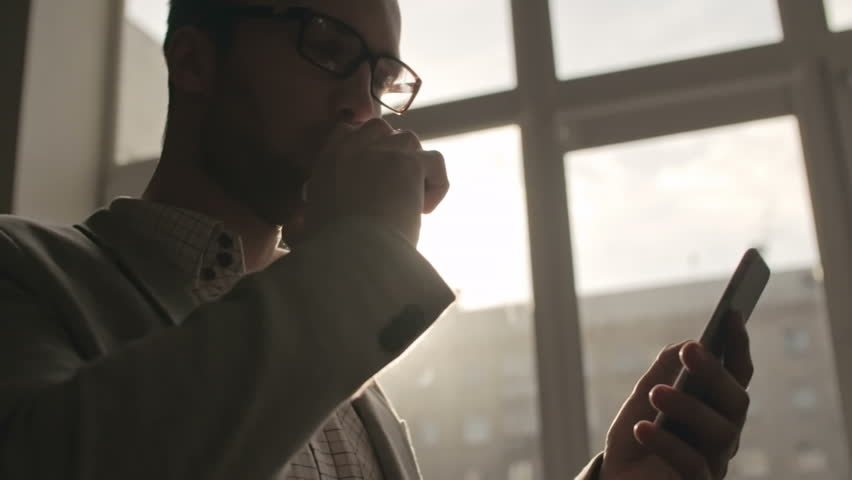Young businessman vaping and text messaging on smartphone near office window, backlit shot on Sony NEX 700 | Shutterstock HD Video #16739893