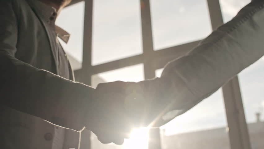 Two businessmen shaking hands to greet each other and talking in office, backlit shot on Sony NEX 700